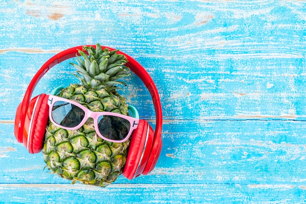 Fondo de verano y viaje de piña con gafas de sol y auriculares en tablero de madera azul con espacio libre.