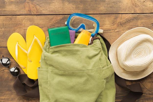 Fondo de verano de viaje de vacaciones mochila de viajero con pasaportes y artículos de vacaciones en la vista superior de la mesa de madera