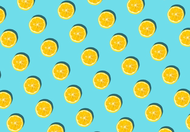Fondo de verano y vitaminas. limón sobre un fondo azul, concepto de comida mínima
