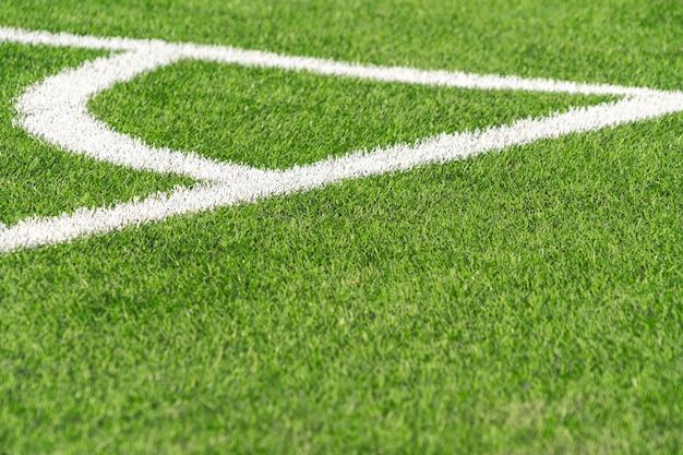 Fondo verde del campo de fútbol del fútbol del césped del césped artificial con el límite blanco de la línea de la esquina. vista superior