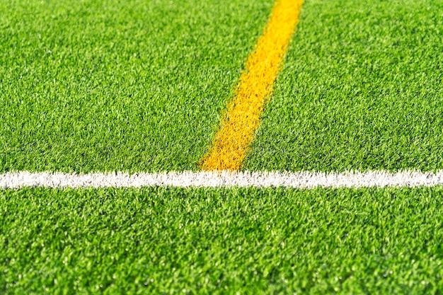 Fondo verde del campo de fútbol del fútbol del césped del césped artificial con el límite de la línea blanca y amarilla. vista superior