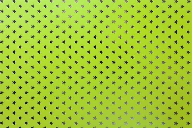Fondo verde claro de papel de aluminio con un patrón de estrellas plateadas.