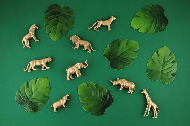 Fondo verde con hojas tropicales y animales exóticos.