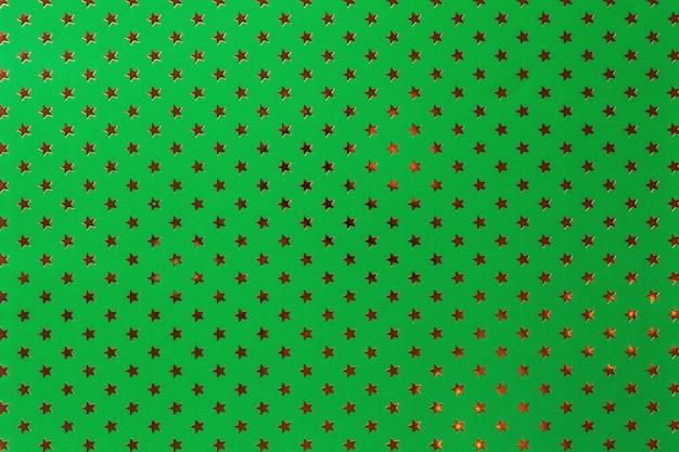 Fondo verde oscuro de papel de aluminio con un patrón de estrellas doradas.