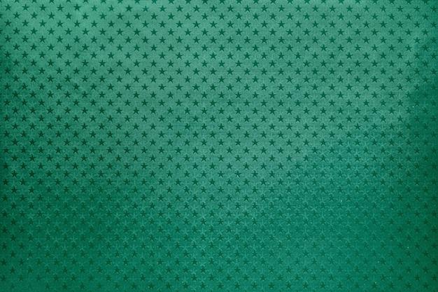 Fondo verde de papel de aluminio con un patrón de estrellas