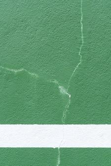 Fondo verde pared deportiva con pintura agrietada.