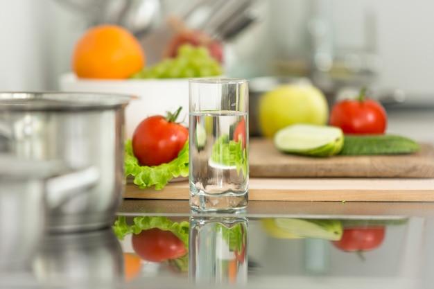 Fondo de verduras frescas junto a la estufa eléctrica en la cocina moderna