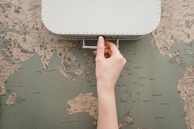 Fondo de viaje con mano junto a una maleta