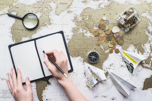 Fondo de viaje con manos escribiendo en un cuaderno en blanco
