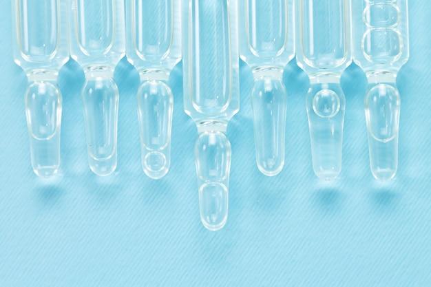 Fondo de viales médicos de vidrio con líquido. vista superior de ampollas de medicina