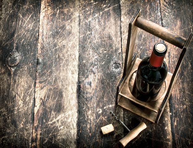 Fondo de vino una botella de vino tinto en un soporte con un sacacorchos sobre un fondo de madera