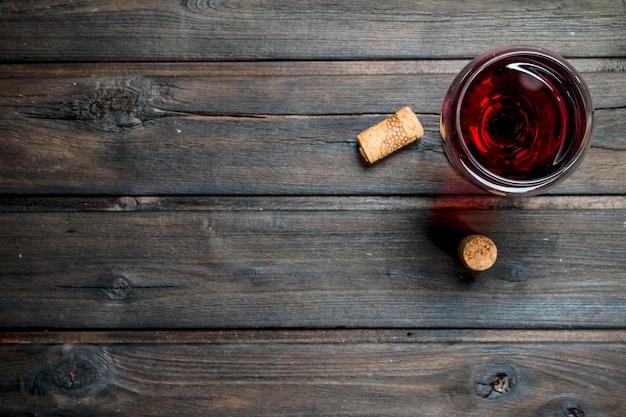 Fondo de vino. una copa de vino tinto con corchos en una mesa de madera.