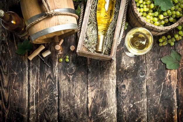 Fondo de vino. vino blanco con un balde de uvas verdes. sobre un fondo de madera.