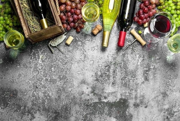 Fondo de vino vino tinto y blanco de uvas frescas sobre un fondo rústico