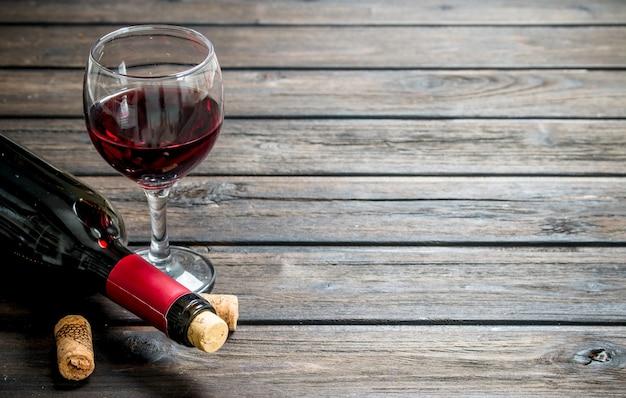 Fondo de vino. vino tinto en una botella con un vaso sobre una mesa de madera.