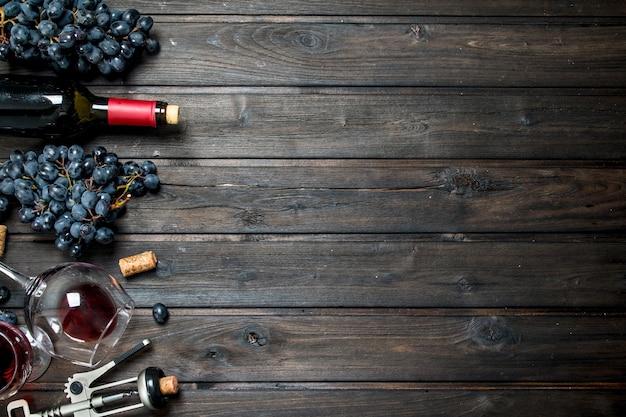 Fondo de vino. vino tinto con sacacorchos de mesa de madera.
