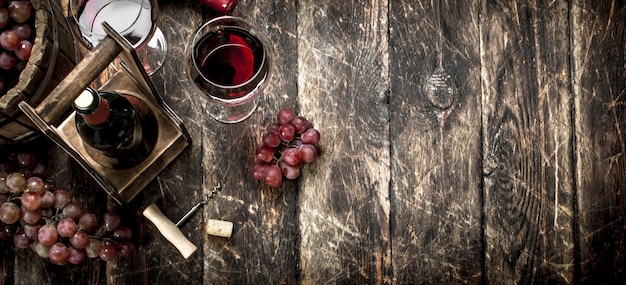 Fondo de vino vino tinto con vasos con uvas sobre un fondo de madera