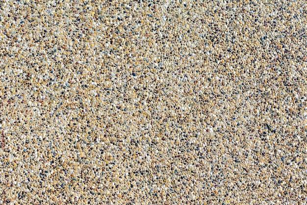 Fondos de pared de piedra arena. pequeños guijarros mezclados con fondo de arena texted.
