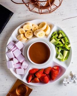 Fondue con frutas sobre la mesa