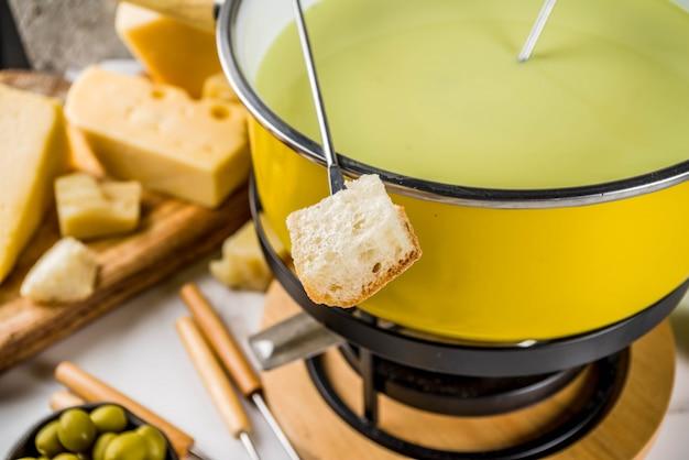 Fondue suiza gourmet en olla de fondue tradicional, con tenedores, varios quesos, aceitunas, pan y uva