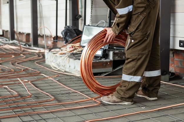 Fontanero colocando tubos de cobre en el piso con calefacción caliente