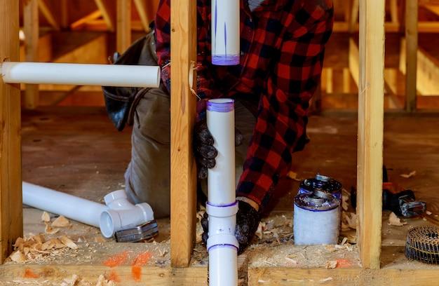 Fontanero instalando tubería de imprimación y pegamento de pvc en casa de construcción