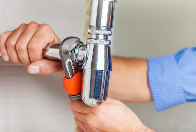 Fontanero, manos, fijación, agua del grifo, en, plano de fondo