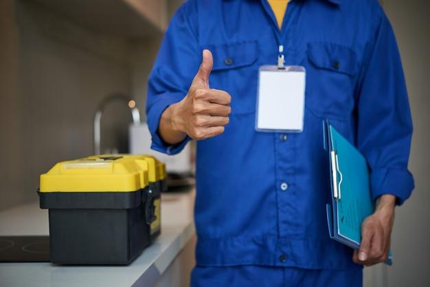 Fontanero masculino irreconocible de pie cerca del fregadero de la cocina y mostrando el pulgar hacia arriba