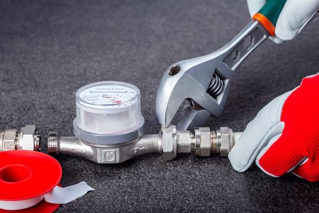 Fontanero en el trabajo instalando medidor de agua. manos del fontanero que usa las llaves mientras que repara las tuberías, visión ascendente cercana.