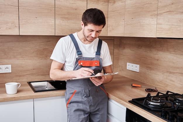 Fontanero en uniforme firma un contrato de servicios en la cocina