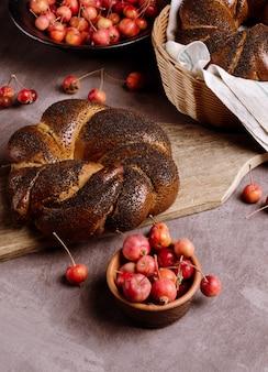 Food style bodegón con bollo con semillas de amapola, pequeñas manzanas silvestres