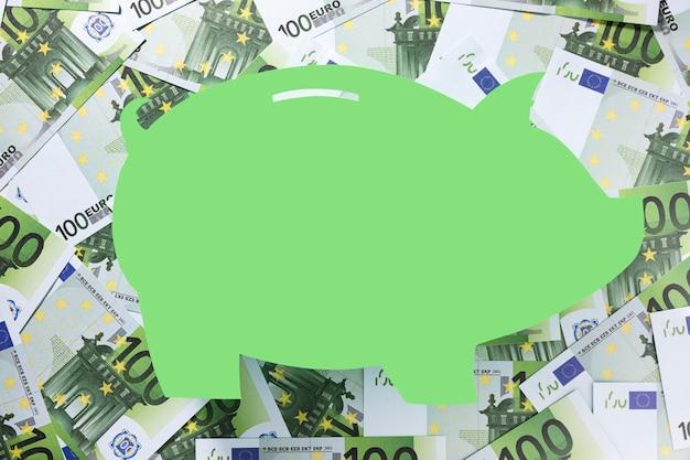 Forma de una alcancía rodeada de euros