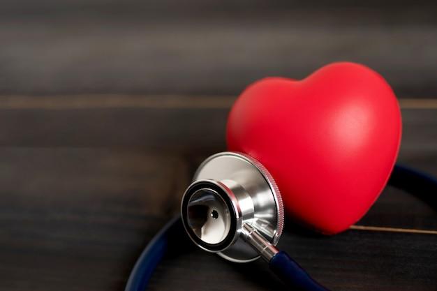 Forma de amor de corazón rojo y estetoscopio de médicos en mesa de madera, control de hipertensión o concepto de seguro de vida hospitalario,