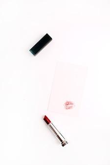 Forma de beso femenino sobre papel con lápiz labial rojo. estilo de vida plano, vista superior