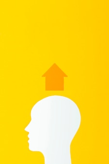 Forma de cabeza con flecha sobre fondo amarillo