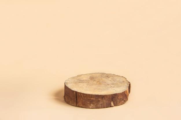 Forma de cilindro de madera cortada sobre fondo beige podio geométrico mínimo
