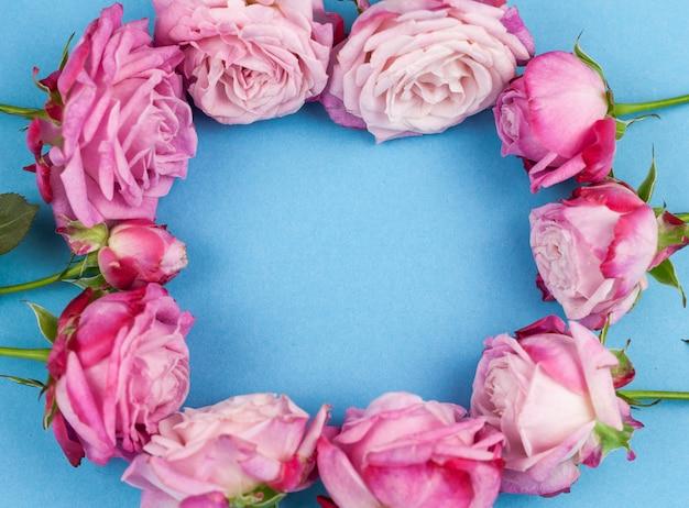 Forma circular hecha de rosa rosa sobre fondo azul