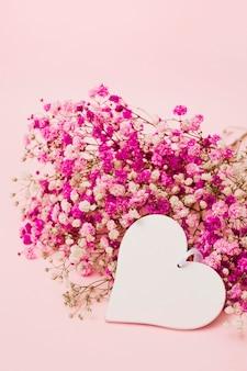 Forma de corazón blanco en blanco con flores de aliento de bebé sobre fondo rosa