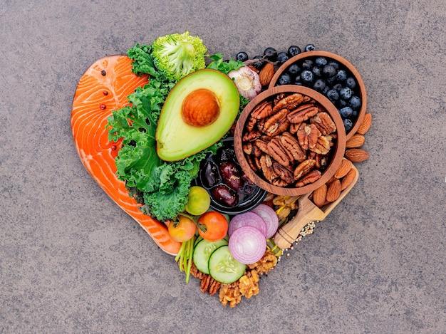 En forma de corazón del concepto de dieta cetogénica baja en carbohidratos sobre fondo de piedra oscura.