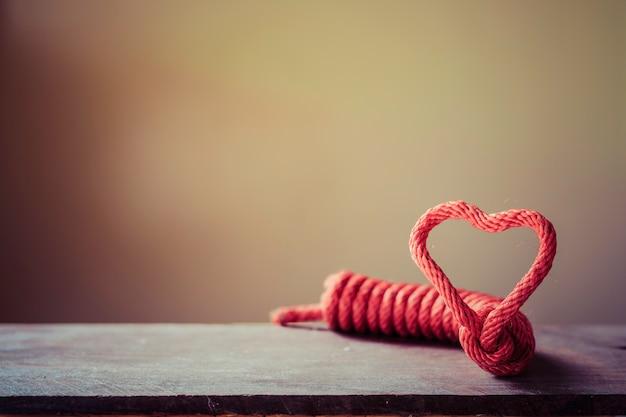 Forma de corazón de la cuerda en el piso de madera marrón