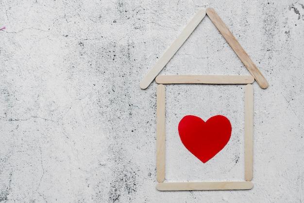 Forma de corazón dentro de la casa hecha con palitos de helado en una pared blanca degradada