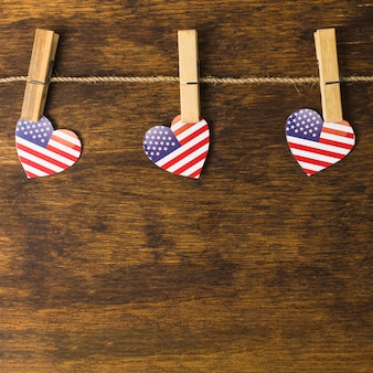 Forma de corazón estadounidense con pinzas para colgar en el tendedero sobre el escritorio de madera