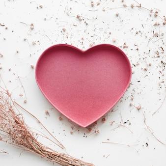 En forma de corazón con flor de rama seca y sobre fondo blanco.