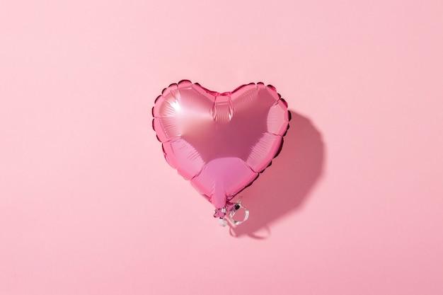 Forma del corazón del globo de aire en un fondo rosado. luz natural. bandera. amor, boda, zona de fotos. vista plana, vista superior
