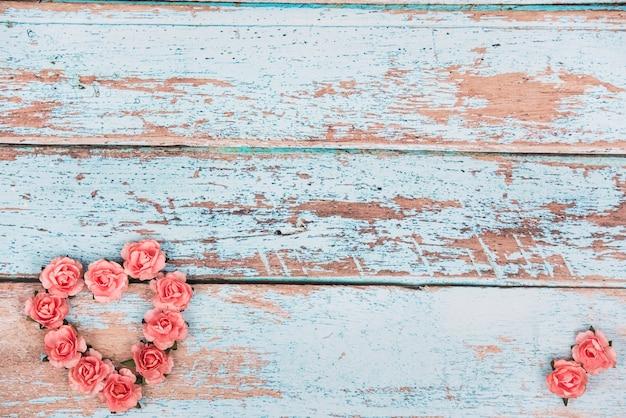 Forma de corazón hecha de capullos de rosas en la mesa
