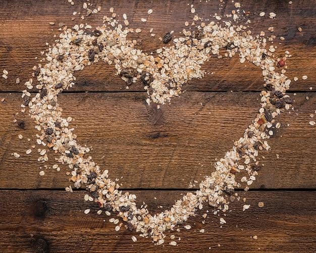 Forma de corazón hecha con comida de avena y nueces en tablón de madera