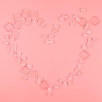 Forma de corazón hecha con diferentes tipos de cubos transparentes sobre fondo coral