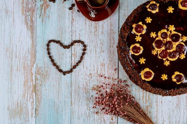 En forma de corazón hecha de granos de café con pastel de chocolate y cereza