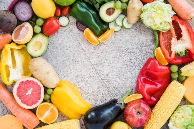 Forma de corazón hecha con verduras de colores sobre fondo texturizado