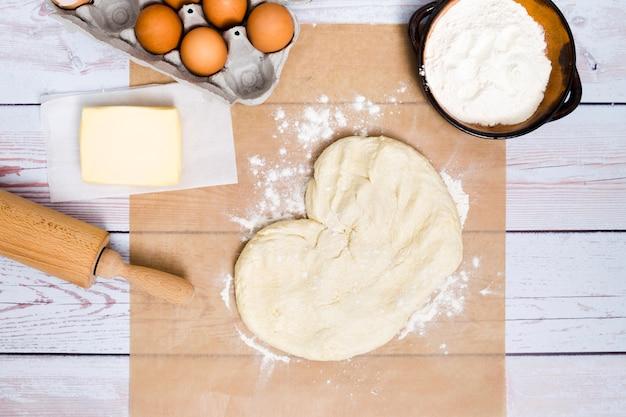 La forma del corazón hizo la masa amasada con ingredientes en tablones de madera.